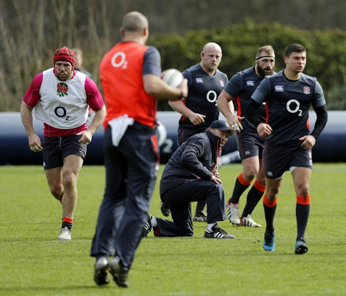 England's Coach Eddie Jones (C) takes to his knee as he watches a drill during a team training session west of London