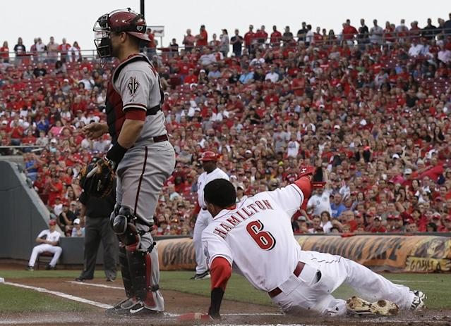 Cincinnati Reds' Billy Hamilton (6) slides safely across home plate as Arizona Diamondbacks catcher Miguel Montero waits for the throw in the first inning of a baseball game, Tuesday, July 29, 2014, in Cincinnati. Hamilton scored on a hit by Todd Frazier. (AP Photo/Al Behrman)