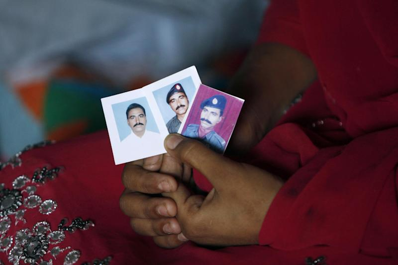 In this Wednesday, Feb. 26, 2014 photo, the daughter of Pakistani police officer Didar Ahmed, who was killed along with three other police officers in early February, displays his pictures, at her home in Karachi, Pakistan. The jacket that Karachi police officer Didar Ahmed was wearing when he was killed was given back to his family after his death. Bullet holes have pierced the sleeves and chest, marking where Ahmed was shot. In some areas the jacket is stained dark with dried blood. (AP Photo/Shakil Adil)
