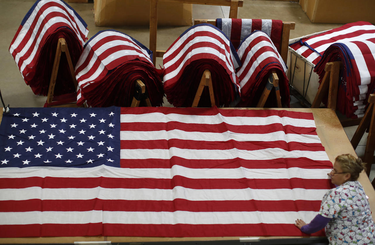 <p>A worker unfurls an American flag at the FlagSource facility in Batavia, Illinois, U.S., on Tuesday, June 27, 2017. (Photo: Jim Young/Bloomberg via Getty Images) </p>