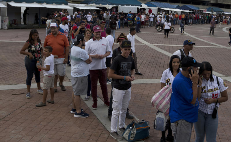 In this Oct. 12, 2018 photo, people line up to buy tickets for the season's opening baseball game between Leones de Caracas and Tiburones de la Guaira in Caracas, Venezuela. Hyperinflation has pulverized incomes while putting ticket prices out of reach for many. (AP Photo/Fernando Llano)
