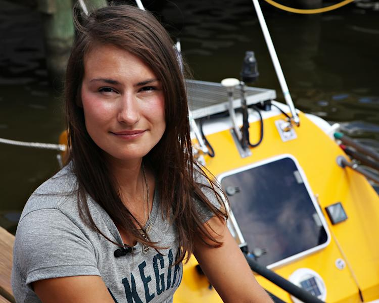 Jenn Gibbons sits on her boat in a marina in South Haven, Mich., on Sunday, Aug. 5, 2012. Gibbons, 27, began a quest to row around the 1,500-mile perimeter of Lake Michigan to raise money for Chicago-based Recovery on Water, a rowing team she co-founded for breast cancer survivors., In July, she was sexually assaulted on her boat, while sleeping along Michigan's Upper Peninsula, but made the decision to continue the journey, part on bicycle, part by boat. She reunited with her boat Aug. 1 in Muskegon, Mich., and is expected back in Chicago in mid-August. (AP Photo/Mimi Weinreb)