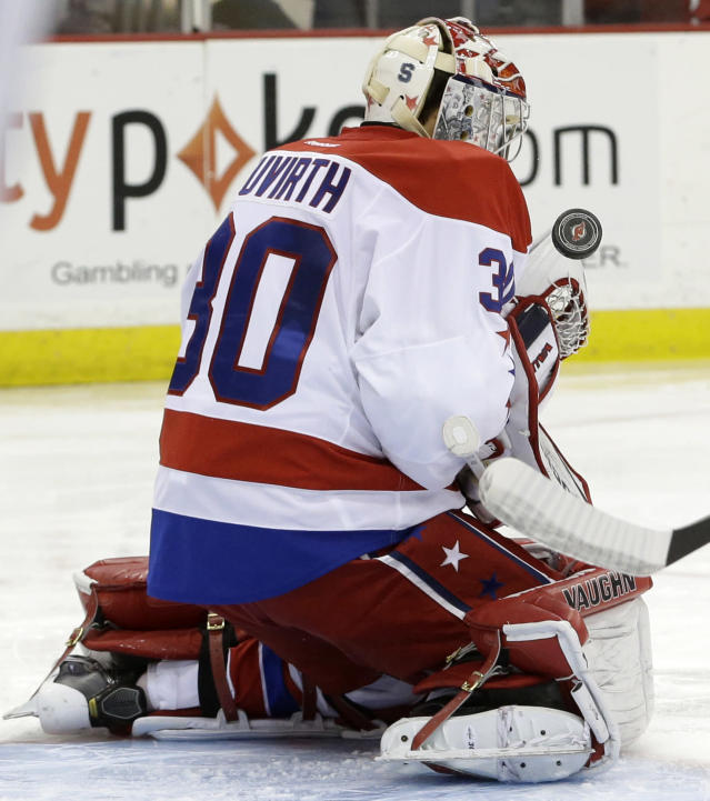 Washington Capitals goalie Michal Neuvirth, of the Czech Republic, makes a save on a shot by the New Jersey Devils during the second period of an NHL hockey game, Friday, Jan. 24, 2014, in Newark, N.J. (AP Photo/Julio Cortez)