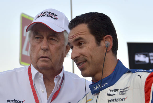 FILE – In this June 10, 2017, file photo, team owner Roger Penske, left, talks with driver Helio Castroneves, of Brazil, on pit road before an IndyCar auto race at Texas Motor Speedway in Fort Worth, Texas. Three-time Indianapolis 500 winner Helio Castroneves will move to Team Penske's sports car program next season, bringing his 20-year full-time IndyCar career to an end. Castroneves will still drive for Penske at the Indianapolis 500. (AP Photo/Randy Holt, File)