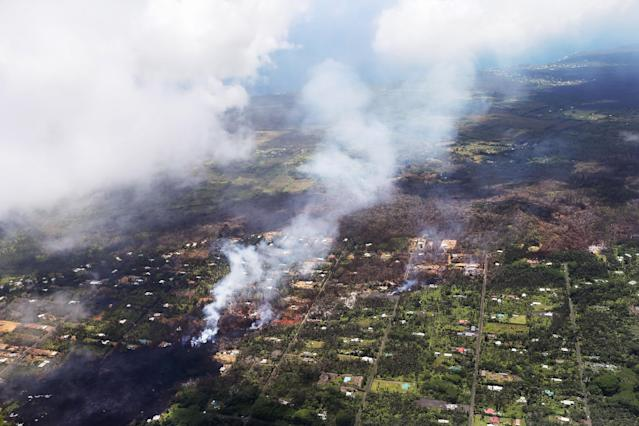 <p>Smoke and volcanic gases rise as lava (L) cools in the Leilani Estates neighborhood, in the aftermath of eruptions and lava flows from the Kilauea volcano on Hawaii's Big Island, on May 11, 2018 in Pahoa, Hawaii. (Photo: Mario Tama/Getty Images) </p>