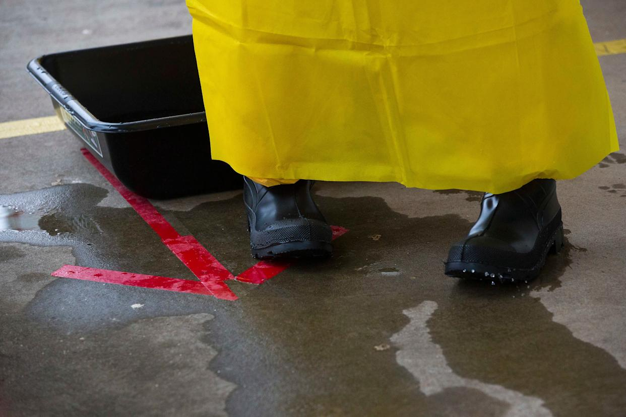 A licensed clinician exits a sanitizing bath after entering the simulated high-risk area of infected Ebola patients on Monday, Oct. 6, 2014, in Anniston, Ala. The Centers for Disease Control and Prevention (CDC) has developed an introductory training course for licensed clinicians. According to the CDC, the course is to ensure that clinicians intending to provide medical care to patients with Ebola have sufficient knowledge of the disease. (AP Photo/Brynn Anderson)
