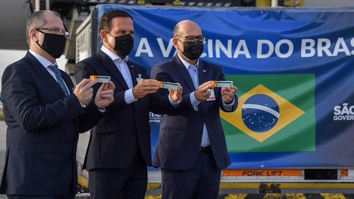 Sao Paulo Governor Joao Doria (C), Sao Paulo state Health Secretary Dr. Jean Gorinchteyn (L), and Butantan Institute Director Dimas Covas (R), pose for photos next to a container carrying doses of the CoronaVac vaccine at Guarulhos International Airport in Guarulhos, near Sao Paulo, Brazil, on December 03, 2020.
