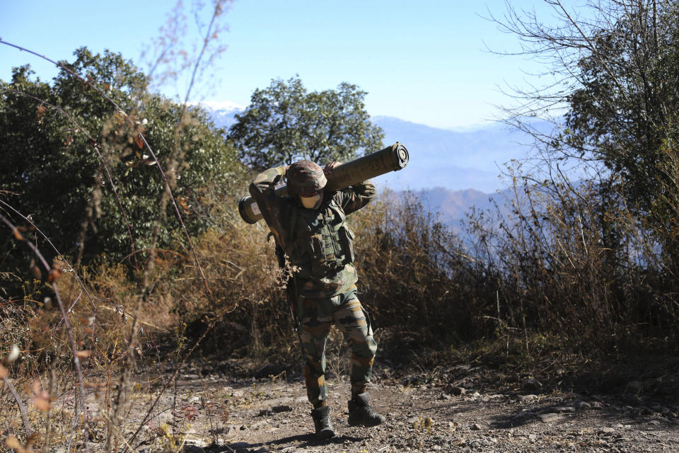 FILE - In this Dec.18, 2020, file photo, an Indian army soldier carries an anti-tank guided missile (ATGM) to his base between India and Pakistan border on the forward post of Balakot, in Poonch, about 250 kilometers (156 miles) from Jammu, India. The machine guns peeking over parapets of small, sandbagged concrete bunkers, and heavy artillery cannons dug deep into Himalayan Kashmir's rugged terrain, have fallen silent. The Line of Control, a highly militarized de facto border that divides the disputed region between the two nuclear-armed rivals India and Pakistan, and a site of hundreds of deaths, is unusually quiet after the two South Asian neighbors in February, 2021 agreed to reaffirm their 2003 cease-fire accord. (AP Photo/Channi Anand, File)