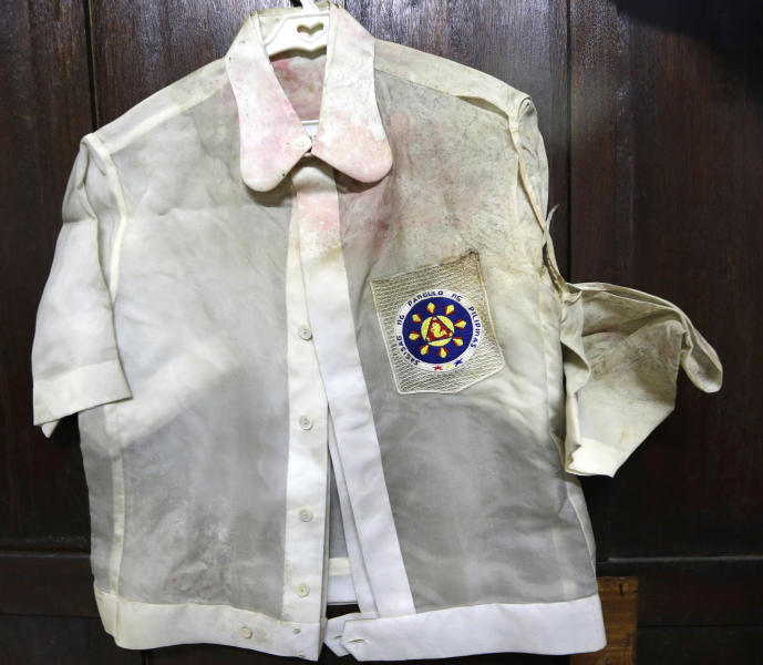 """In this photo taken Sept. 19, 2012, native Filipino attire called """"Barongs"""" which had been often worn in public during the two-decade rule of the late strongman Ferdinand Marcos, is revealed from a section of the National Museum in Manila, Philippines. Termites, storms and government neglect have damaged hundreds of pieces of Marcos' """"barongs"""" as well as former first lady Imelda Marcos's legendary stash of shoes, expensive gowns and other vanity possessions, which were left to oblivion after she and her dictator husband were driven to U.S. exile by a 1986 popular revolt. (AP Photo/Bullit Marquez)"""