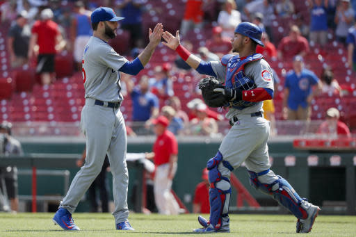 Chicago Cubs relief pitcher Brandon Morrow, left, celebrates with catcher Willson Contreras, right, after closing the ninth inning of a baseball game against the Cincinnati Reds, Sunday, May 20, 2018, in Cincinnati. (AP Photo/John Minchillo)