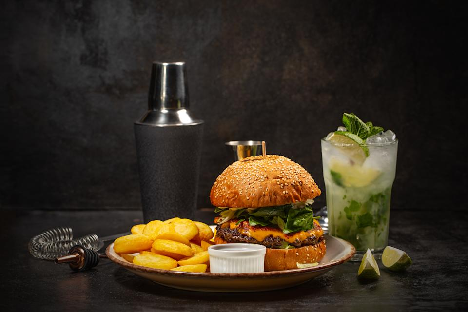 Dinner with burger and glass of mojito cocktail on dark background