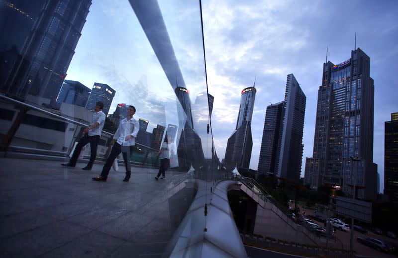 People cross a bridge at Pudong financial district in Shanghai