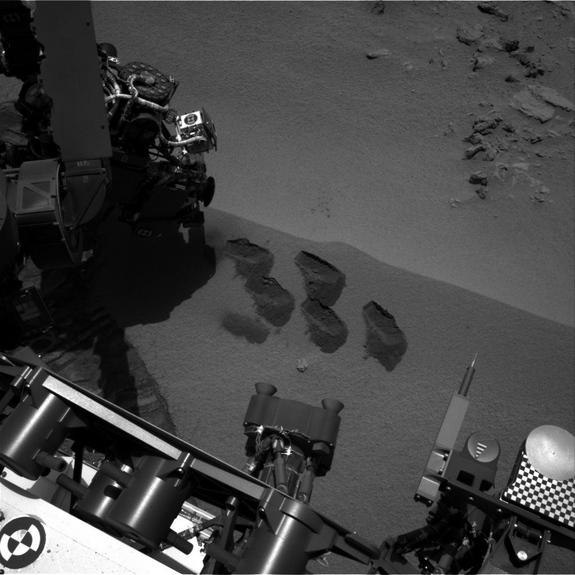 """Bite-marks on Mars. NASA's Mars rover Curiosity used a mechanism on its robotic arm to dig up five scoopfuls of material from a patch of dusty sand called """"Rocknest."""" Each of the pits is about 2 inches (5 centimeters) wide. A sample from that"""