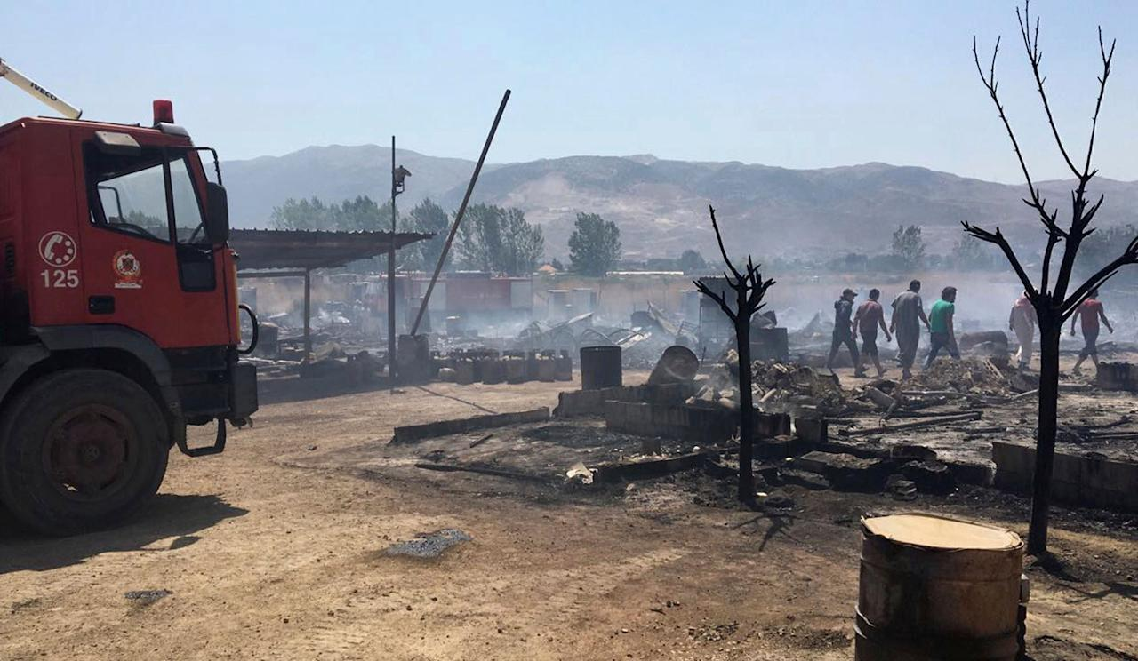 <p>This photo provided by the Qab Elias Emergency Services, shows Lebanese Civil Defense workers putting out a fire in a Syrian refugee camp in Qab Elias, a village in the Bekaa Valley, Lebanon in Qab Elias, Lebanon, Sunday, July 2, 2017. Lebanon's state news agency and the Red Cross say a major fire has broken out in a Syrian refugee settlement, killing at least one person and sending large plumes of black smoke into the sky. (Qab Elias Emergency Services via AP) </p>