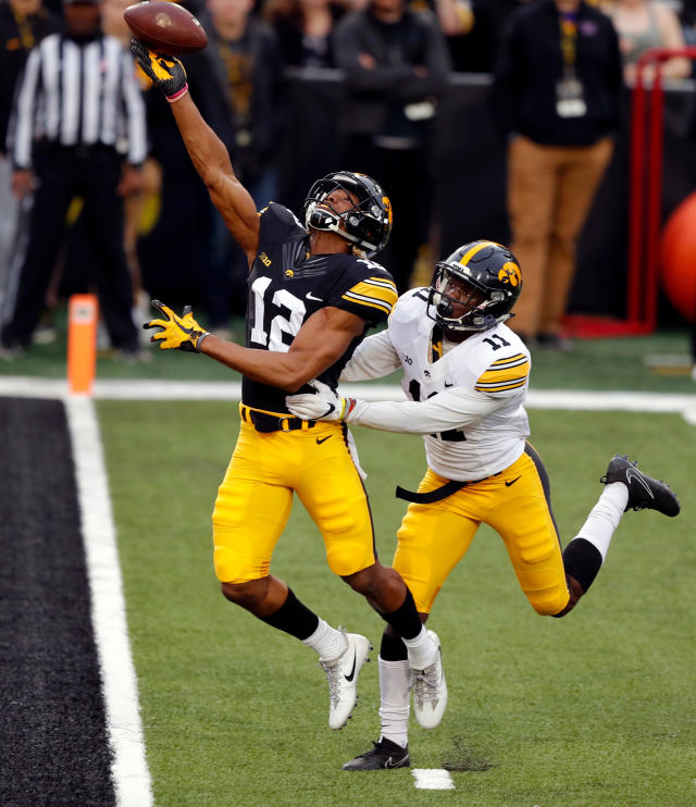 Iowa wide receiver Brandon Smith (12) tries to make a reception over defensive back Michael Ojemudia (11) during the team's NCAA college football spring scrimmage Friday, April 20, 2018, in Iowa City, Iowa. The pass was incomplete. (AP Photo/Charlie Neibergall)
