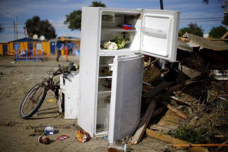 A refrigerator lies on a damaged street after an earthquake hit areas of central Chile, in Tongoy town