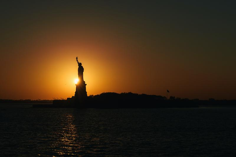 The Statue of Liberty silhouette by the setting sun in New York harbor