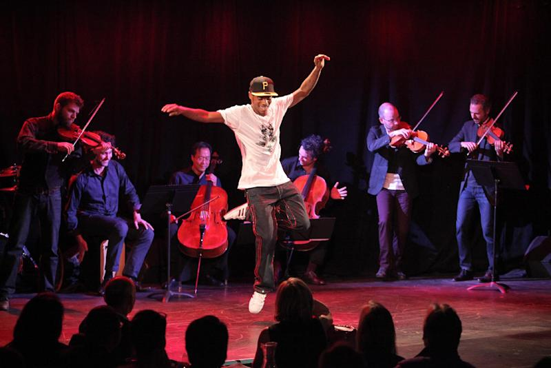 This April 2, 2013 photo released by New York City Center shows Lil Buck, center, performing with Yo-Yo Ma, background at center left, at Poisson Rouge nightclub in New York. (AP Photo/New York City Center, Erin Baiano)