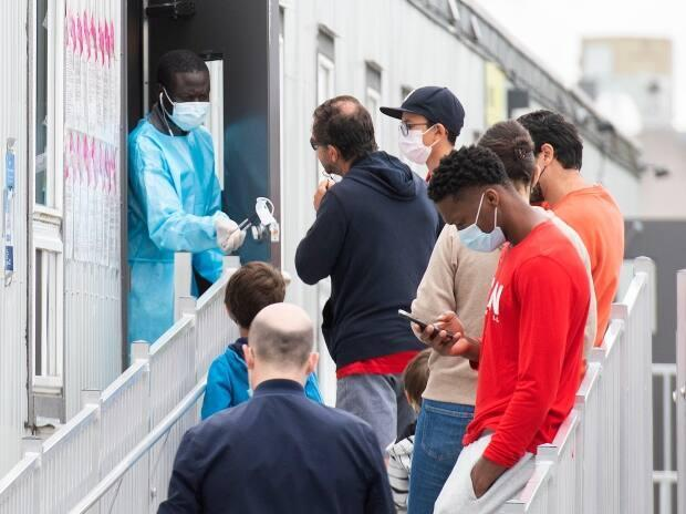 People wait to be tested for COVID-19 at a clinic in Montreal on Sunday. Quebec public health reported 154 new infections on Monday. (Graham Hughes/The Canadian Press - image credit)