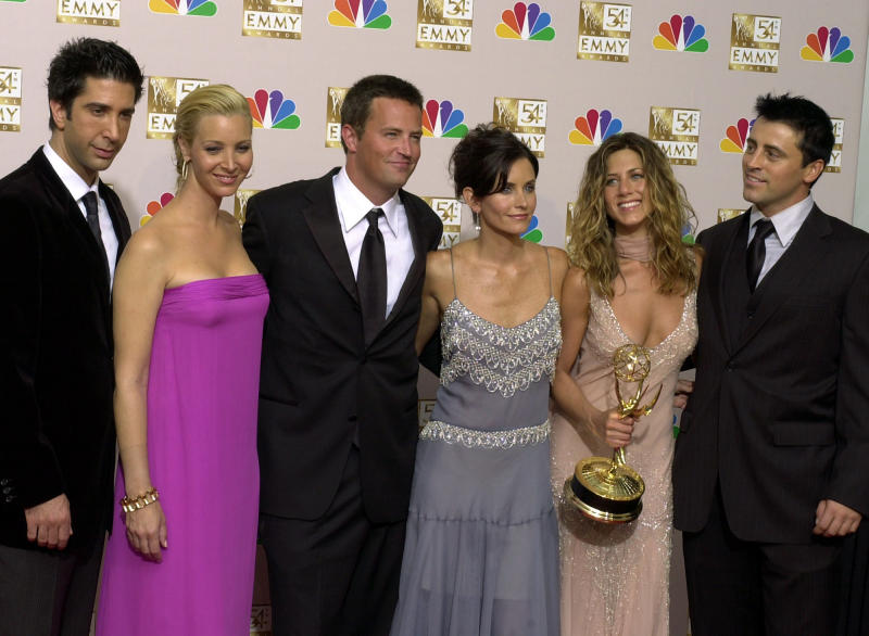 """FILE - In this Sept. 22, 2002 file photo, the stars of """"Friends,"""" from left, David Schwimmer, Lisa Kudrow, Matthew Perry, Courteney Cox Arquette, Jennifer Aniston and Matt LeBlanc pose after the show won outstanding comedy series at the 54th Annual Primetime Emmy Awards, at the Shrine Auditorium in Los Angeles.  If you're a """"Friends"""" superfan, there are lots of ways to celebrate the show's 25th anniversary on Sept. 22, 2019. Warner Bros. has partnered with a range of companies to celebrate the quarter-century mark.  (AP Photo/Reed Saxon, file)"""