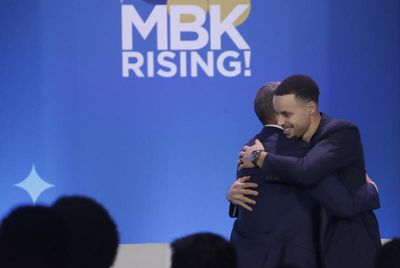 Former President Barack Obama, left, hugs Golden State Warriors basketball player Stephen Curry after speaking at the My Brother's Keeper Alliance Summit in Oakland, Calif., Tuesday, Feb. 19, 2019. (AP Photo/Jeff Chiu)