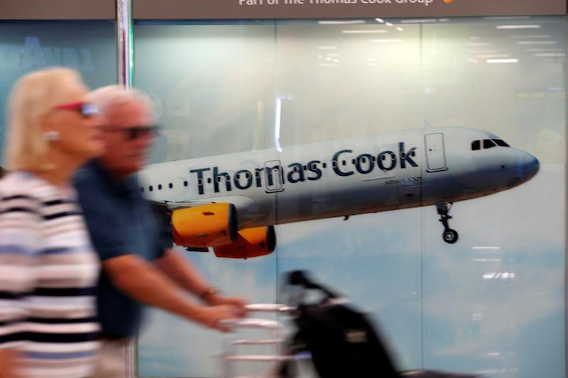 Passengers at Mallorca airport walk past a Thomas Cook ad. Photo: Enrique Calvo/Reuters