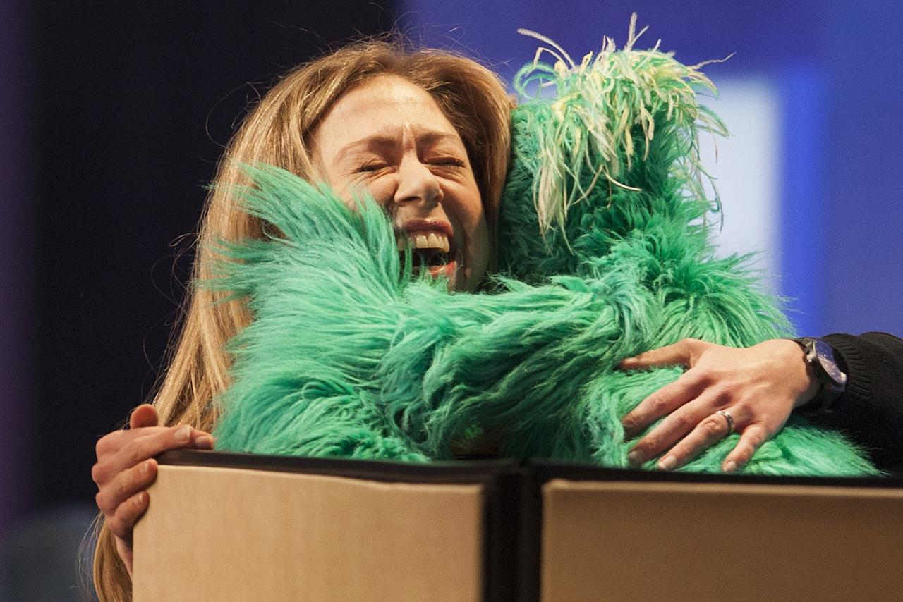"""Chelsea Clinton, daughter of former U.S. President Bill Clinton, hugs """"Rosita the Muppet"""" on stage during the Clinton Global Initiative 2013 (CGI) in New York"""