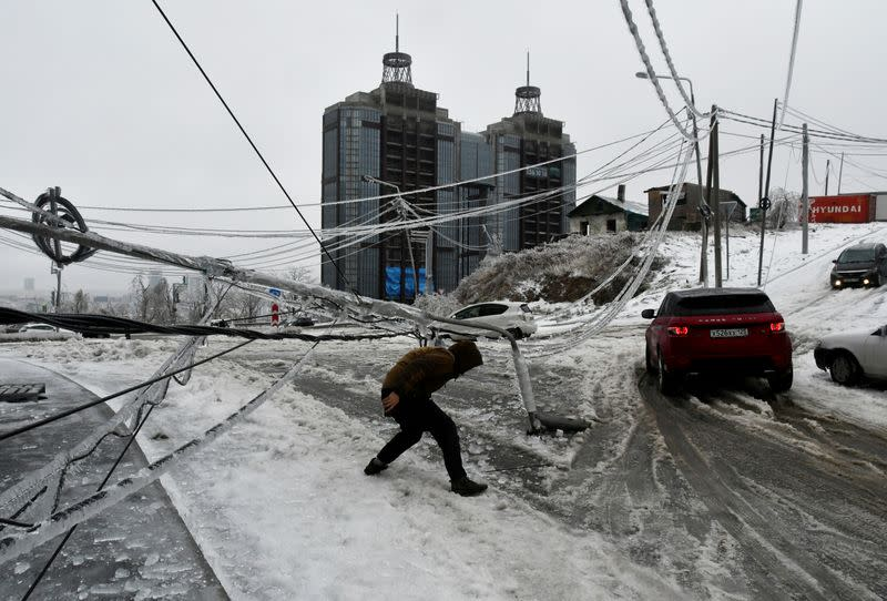 FILE PHOTO: A man walks under a damaged power pole covered with ice after freezing rain in Vladivostok