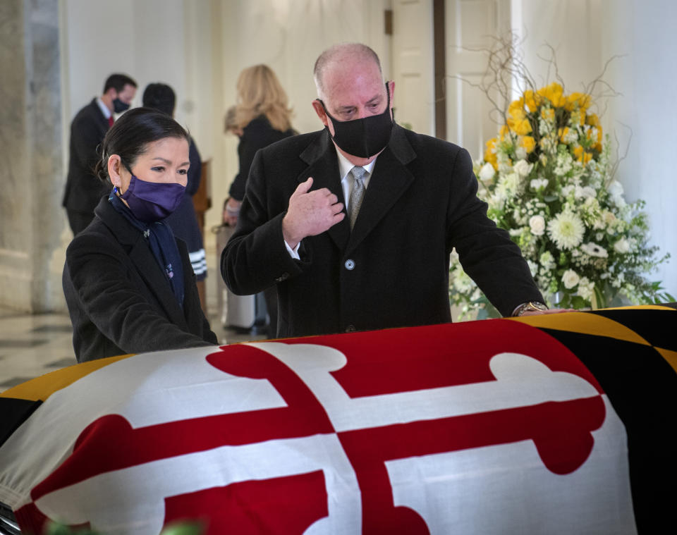 Gov. Larry Hogan, center, with wife Yumi, left, pays respects to the late Senate President Emeritus Thomas V. Mike Miller, Jr., under the dome of the statehouse at the Maryland Statehouse in Annapolis, Md., on Friday, Jan. 22, 2021. Miller was a state legislator for 50 years. A Democrat, he served as president of the Maryland Senate for 33 years. He announced he was stepping down from the post in 2019, but he remained a senator until December. (Bill O'Leary/The Washington Post via AP, Pool)