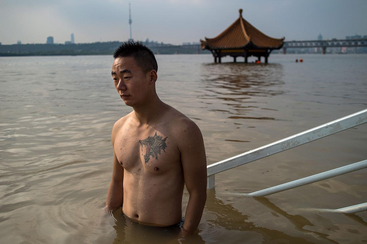 <p>A man stands in the Yangtze River along the River Beach Park in Wuhan, Hubei Province, China on July 3, 2017, after heavy rains caused the water levels to rise. (Photo: STR/AFP/Getty Images) </p>