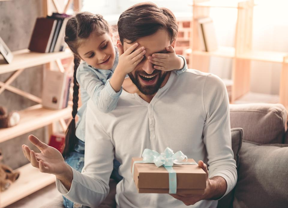Cute little girl is giving her handsome father a gift box. Both are sitting on couch at home and smiling