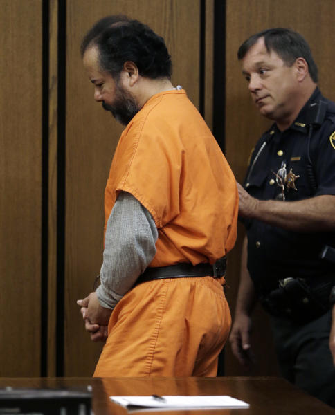 Ariel Castro, left, is escorted out of the courtroom by a sheriff's deputy Wednesday, July 24, 2013, in Cleveland. Attorneys for Castro, who is accused of holding three women captive in his home for more than a decade, have told a judge that plea negotiations in the case are still ongoing. Castro has pleaded not guilty to nearly 1,000 counts of kidnap, rape and other crimes. (AP Photo/Tony Dejak)