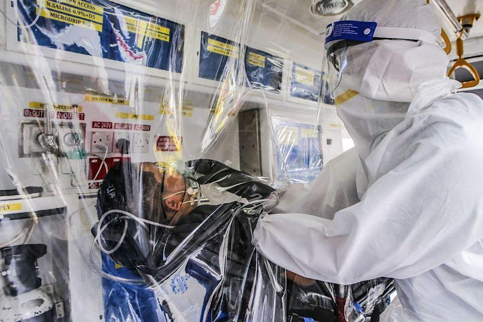 Paramedic Norsahril Abdul Razak, in full Personal Protection Equipment, demonstrates how a suspected Covid-19 case is handled in the repurposed ambulance.