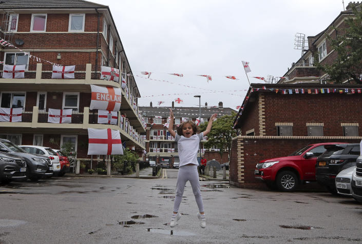 Marianne Hicks-Brisson jumps in the air as she poses for a photograph in the Kirby Estate adorned with English Cross of St. George flags in support of the England soccer team competing at the Euro 2020 soccer championships in Bermondsey, south London on June 29, 2021. (AP Photo/Tony Hicks)