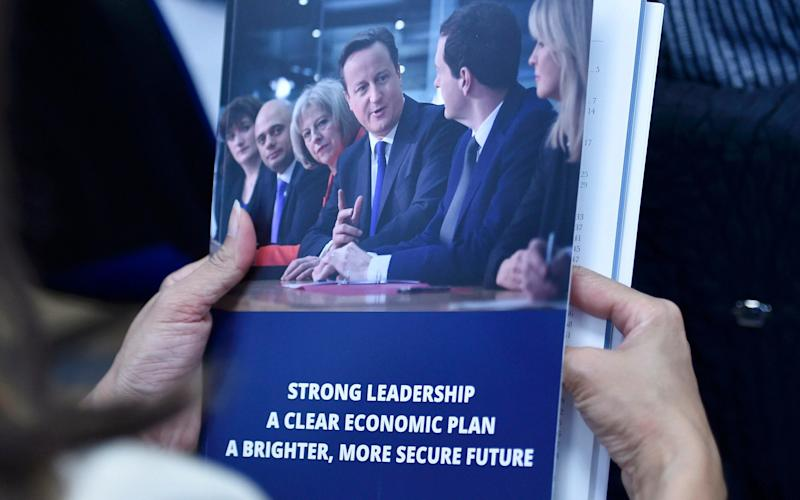A woman holds a copy of Britain's Conservative Party election manifesto in Swindon, western England, April 14, 2015.  - TOBY MELVILLE