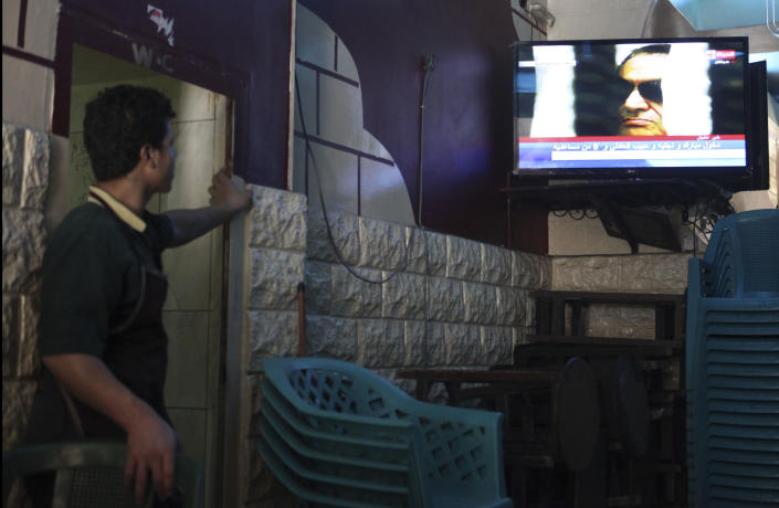 FILE - In this June 2, 2012 file photo, a worker in a downtown cafe watches the final session of the trial of former Egyptian President Hosni Mubarak, in Cairo, Egypt. The 2011 uprising led to the quick ouster of autocrat Mubarak. A decade later, thousands are estimated to have fled abroad to escape a state, headed by President Abdel Fattah el-Sissi, that is even more oppressive. (AP Photo/Thomas Hartwell, File)