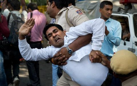 An Indian policeman takes away a Congress party worker during a protest against India's junior external affairs minister MJAkbar in New Delhi - Credit: Manish Swarup/AP