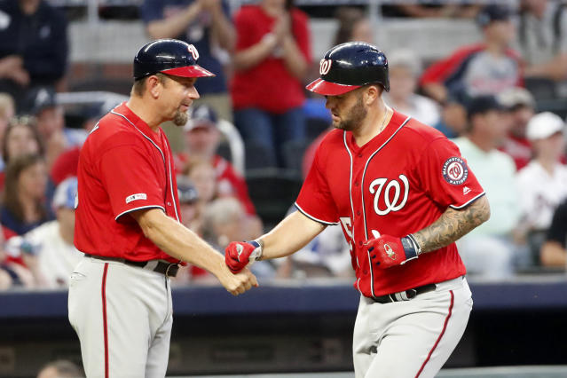 Washington Nationals first baseman Matt Adams (15), right, celebrates with Washington Nationals third base coach Bob Henley (13) as he rounds the bases after hitting a home run in the fourth inning of a baseball game against the Atlanta Braves Saturday, July 20, 2019, in Atlanta. Washington won 5-3. (AP Photo/John Bazemore)