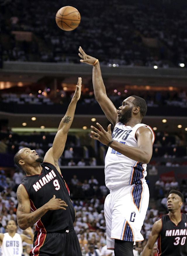 Charlotte Bobcats' Al Jefferson, right, shoots over Miami Heat's Rashard Lewis, left, during the first half in Game 3 of an opening-round NBA basketball playoff series in Charlotte, N.C., Saturday, April 26, 2014. (AP Photo/Chuck Burton)