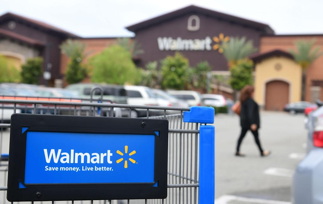 A woman walks past a shopping cart in the parking lot of a Walmart Supercenter in Rosemead, California on May 23, 2019.