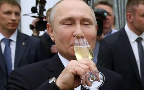 Russian President Vladimir Putin drinks champaigne during a meeting with paralympic athlets at the Kremlin - Credit: Mikhail Svetlov/Getty