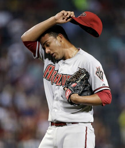 Arizona Diamondbacks pitcher Randall Delgado wipes his brow after giving up a home run to Atlanta Braves' Andrelton Simmons in the fifth inning of a baseball game, Friday, June 28, 2013, in Atlanta. (AP Photo/David Goldman)