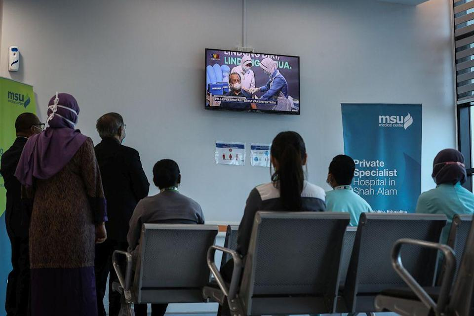 Staff at the MSU Medical Centre watch a live broadcast of Prime Minister Tan Sri Muhyiddin Yassin receiving his Covid-19 jab in Shah Alam February 24, 2021. ― Picture by Yusof Mat Isa