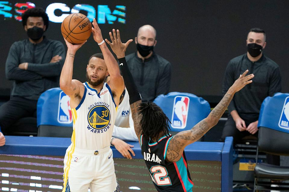Warriors guard Stephen Curry (30) shoots over Grizzlies guard Ja Morant (12) during the third quarter on Sunday.