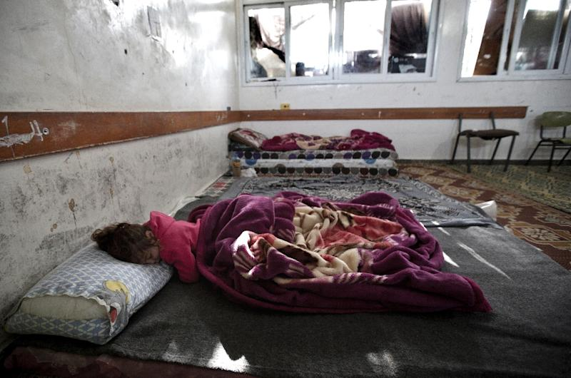 A Palestinian girl sleeps at a makeshift bedroom inside a UN-run school in Gaza City on February 25, 2015 (AFP Photo/Mahmud Hams)
