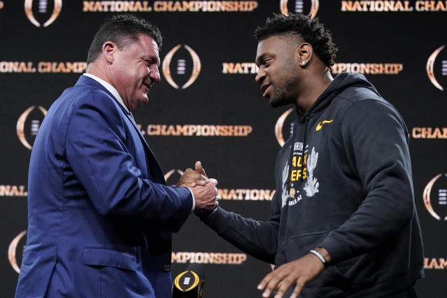 LSU head coach Ed Orgeron, left, greets linebacker Patrick Queen after a news conference for the NCAA College Football Playoff national championship game Tuesday, Jan. 14, 2020, in New Orleans. LSU won 42-25 over Clemson on Monday. (AP Photo/David J. Phillip)