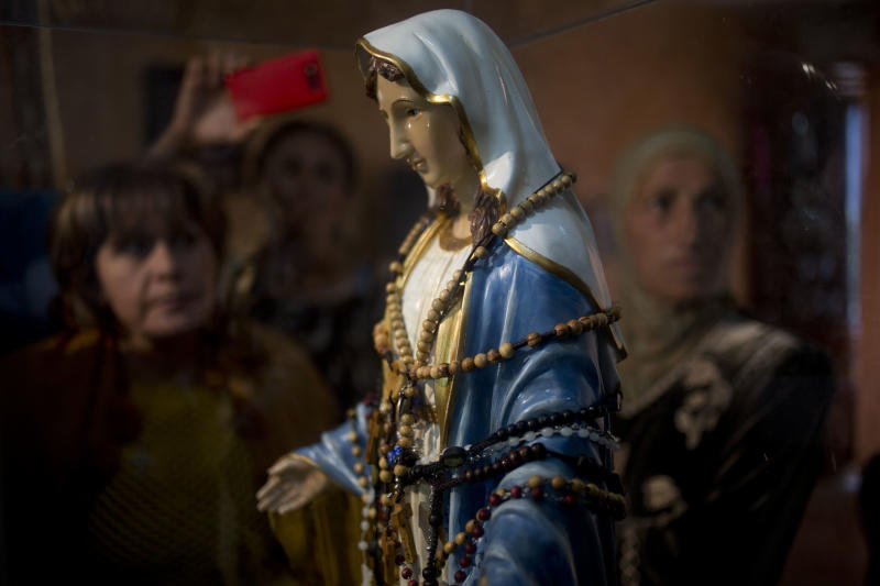 "Christian worshipers gather next to a statue of the Virgin Mary, that residents say ""weeps"" oil, inside an apartment belonging to the Khoury family, in Tarshiha, a small town in northern Israel,Tuesday, Feb. 11, 2014. The family says it is most striking when a ""tear"" seems to roll down the statue's cheek. It says some 2,000 people have come to see the statue over the last week. (AP Photo/Ariel Schalit)"