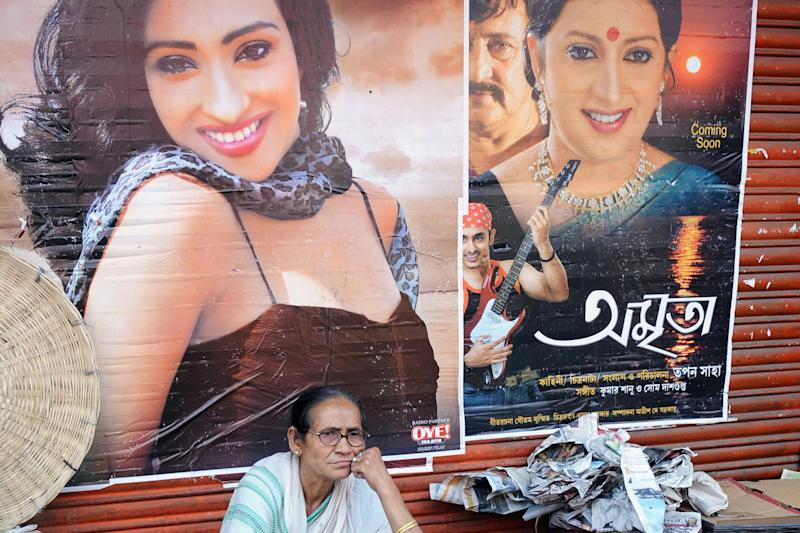 An Indian woman rests in front of Bengali movie posters. Bengali cinema, nicknamed Tollywood, is a portmanteau of the words Tollygunge and Hollywood, which origins dating back to 1932: Dibyangshu Sarkar/AFP/Getty Images