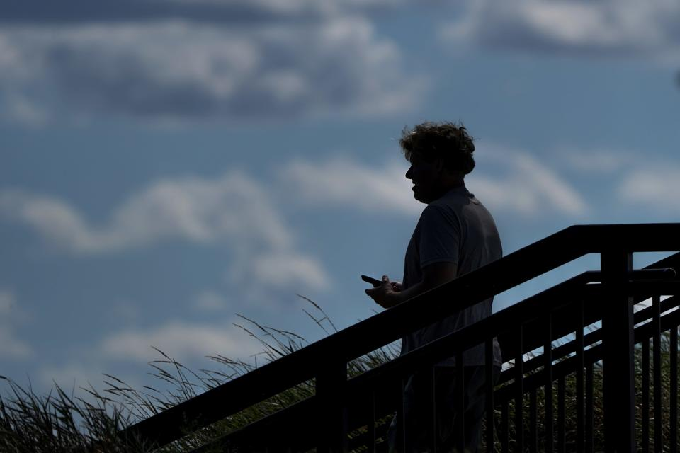 A pedestrian uses his phone in Kilbourn Reservoir Park Wednesday, Sept. 8, 2021, in Milwaukee. The City of Milwaukee has placed wireless broadband hotspots in the park during the pandemic. (AP Photo/Morry Gash)