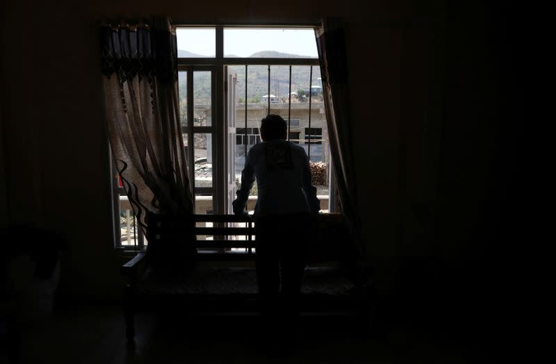 A Myanmar national who said he recently fled to India looks out from a window of a house at an undisclosed location